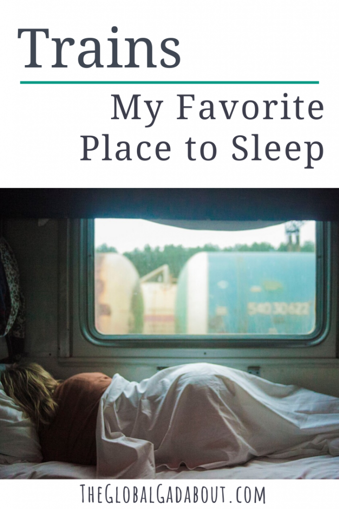 "White background with the words ""Trains: My Favorite Place to Sleep"" and ""TheGlobalGadabout.com"". Between the two phrases is a photo of a woman sleeping on a train, her back to the camera, covered by a sheet with a large window above her."