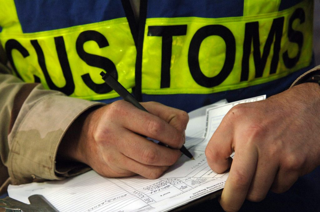 Close up on a customs official's hands filling out paperwork.