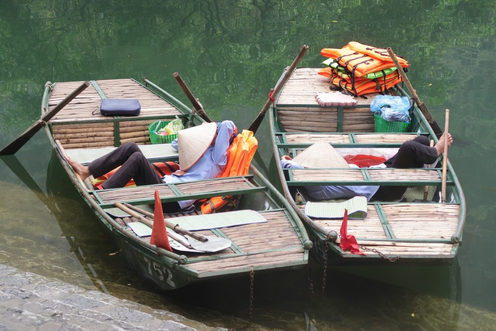 2 Asian row boats floating in shallow water. A person is asleep in each one with a conical hat covering their faces.