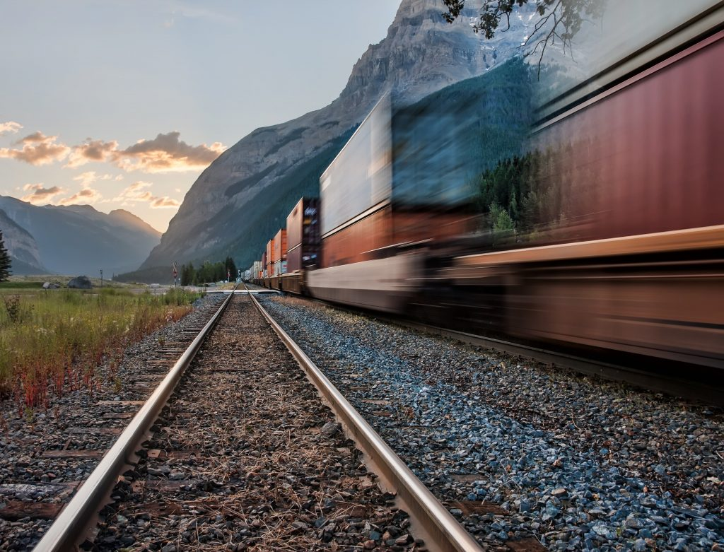 From the low perspective of the tracks, a train blurred by motion is heading toward the sun setting behind distant mountains.