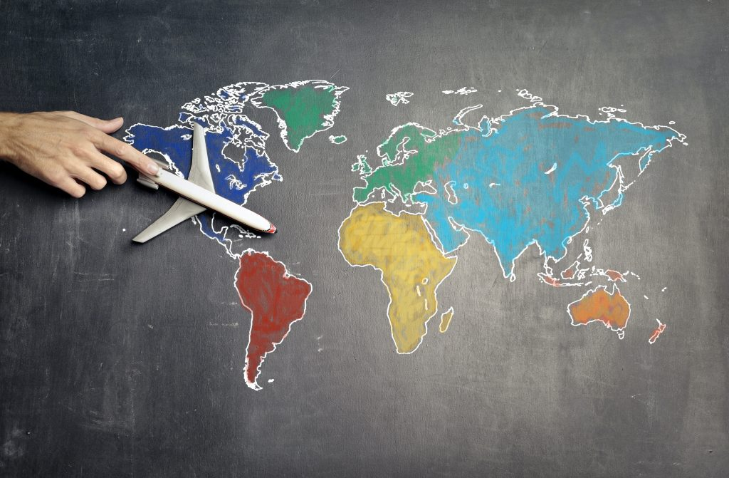 A colorful world map drawn on a chalkboard. A hand is push a toy airplane across the map.