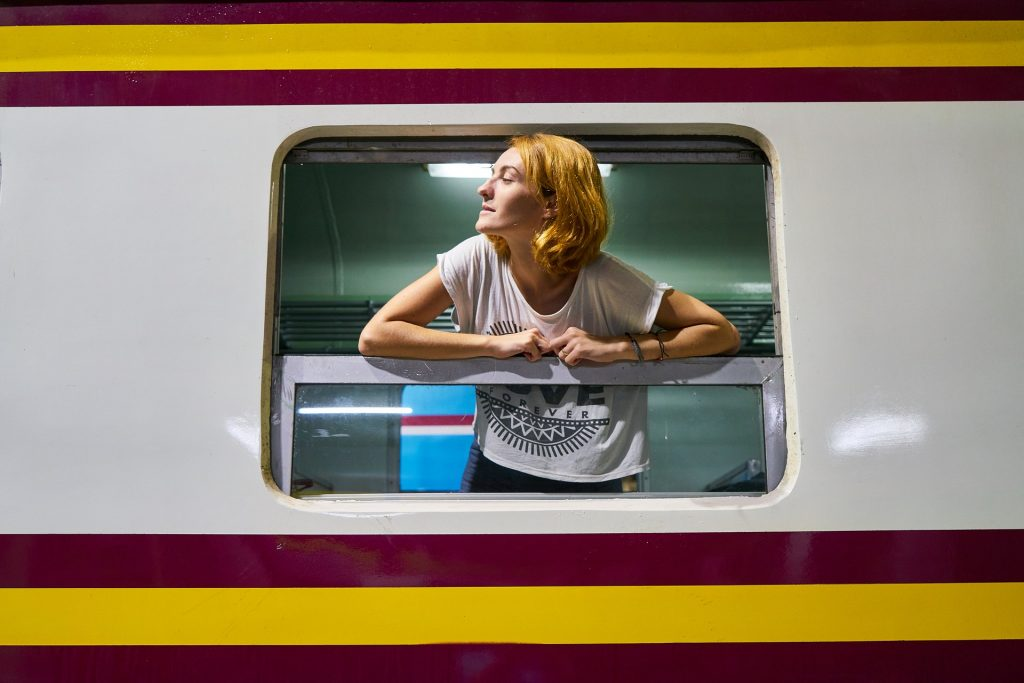 A woman leans out the window of a train, looking into the distance.