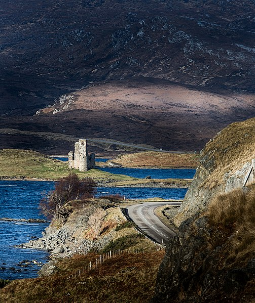 A windy coastal road in Scotland with a castle in the foreground and a tall mountain in the background.