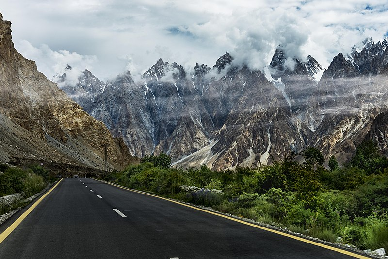 The Karakoram Highway between China & Pakistan with jagged, cloudy mountains all around.