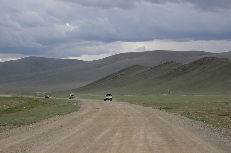 A dirt road below rounded mountains in Mongolia with three cars in the distance.