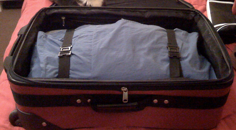 A neat bundle of clothes in a suitcase.