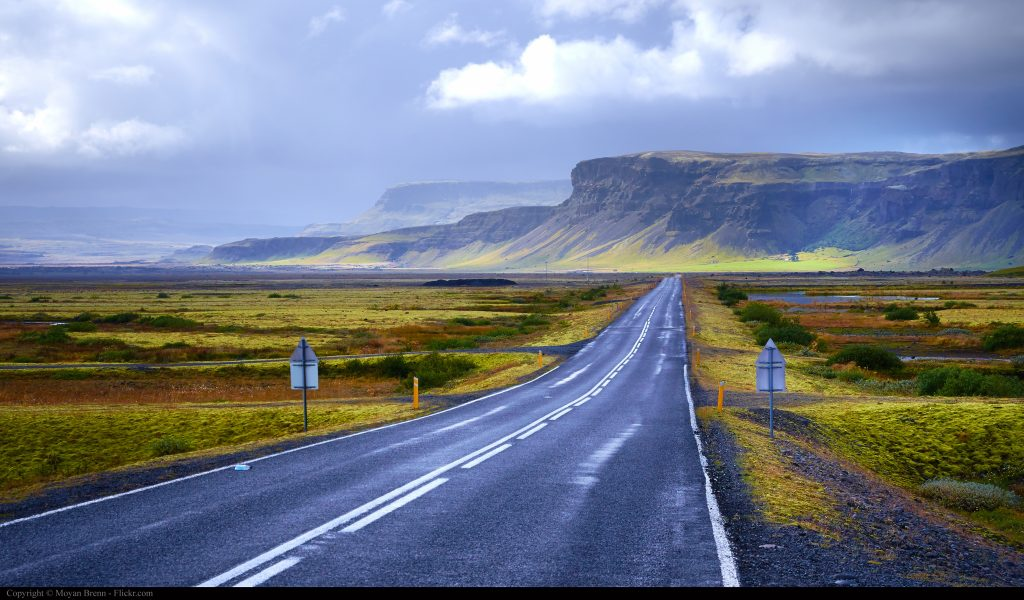 The Ring Road in Iceland with mossy green fields and mountains in the background.