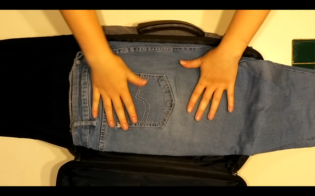 Hands placing pants into a suitcase using the bundle method