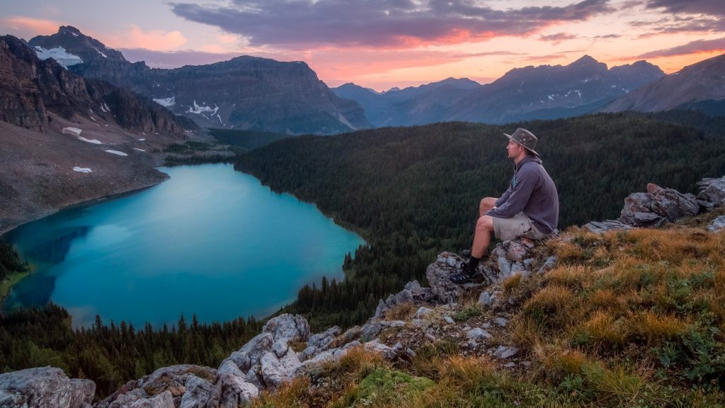 A man sitting on top of a mountain at sunset, looking out at distant mountains and a lake below.