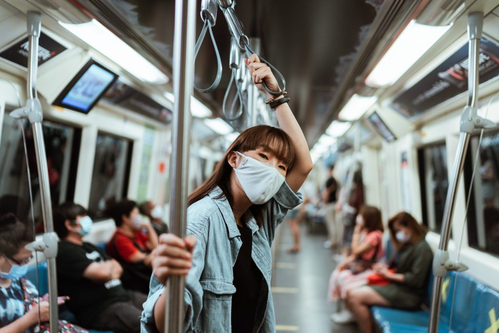 A woman in a mask riding the subway with other masked passengers in the background.