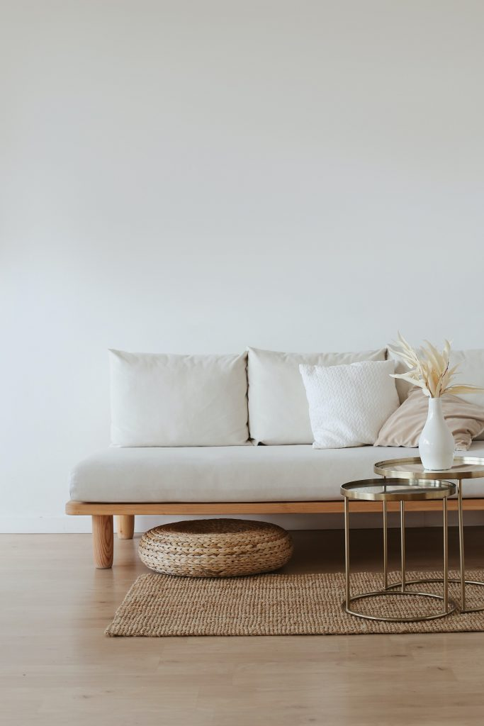 A white wall with minimalist decor: a white couch, rug & coffee table.