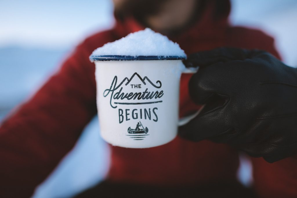 "An out of focus person in a red jacket and black gloves holds a white mug full of snow with the words ""The Adventure Begins"" in focus in the foreground."