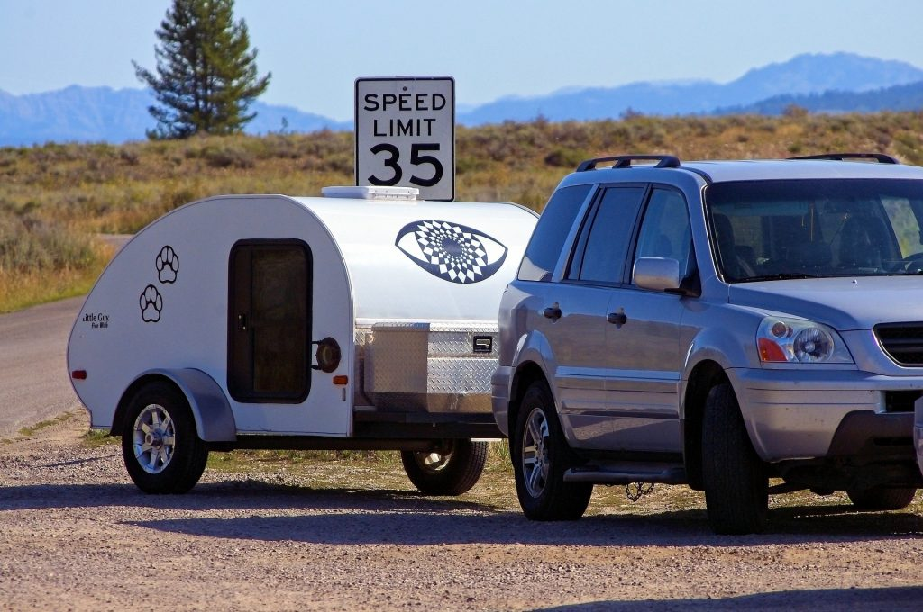 An SUV pulling a travel trailer.